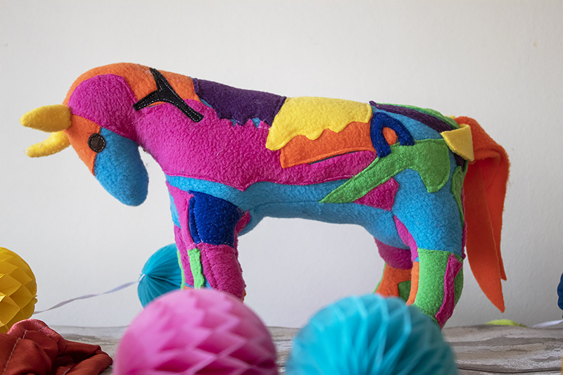 Multicoloured toy horse with a white background for a blog post about Petplan Equine Insurance.