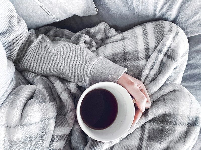 woman holding black coffee under a grey blanket on a grey sofa