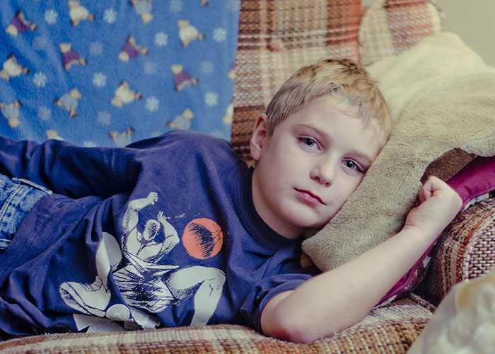 boy lying on the sofa with his head on a cushion facing the camera for a blog post on childhood illnesses