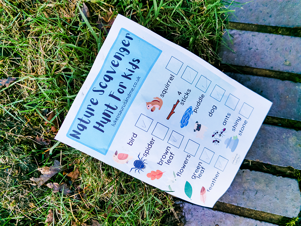 a printed version of a nature scavenger hunt rests on some grass, a few of the items have been ticked off in pencil