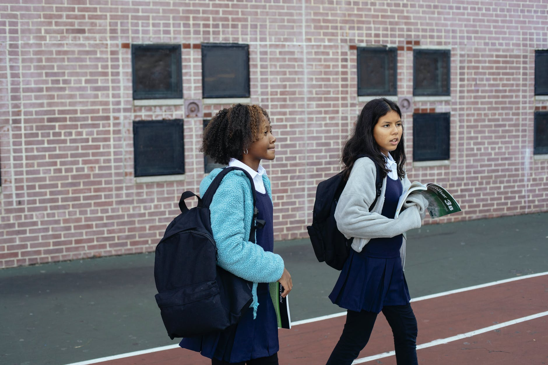 diverse girls in uniforms with backpacks walking on stadium