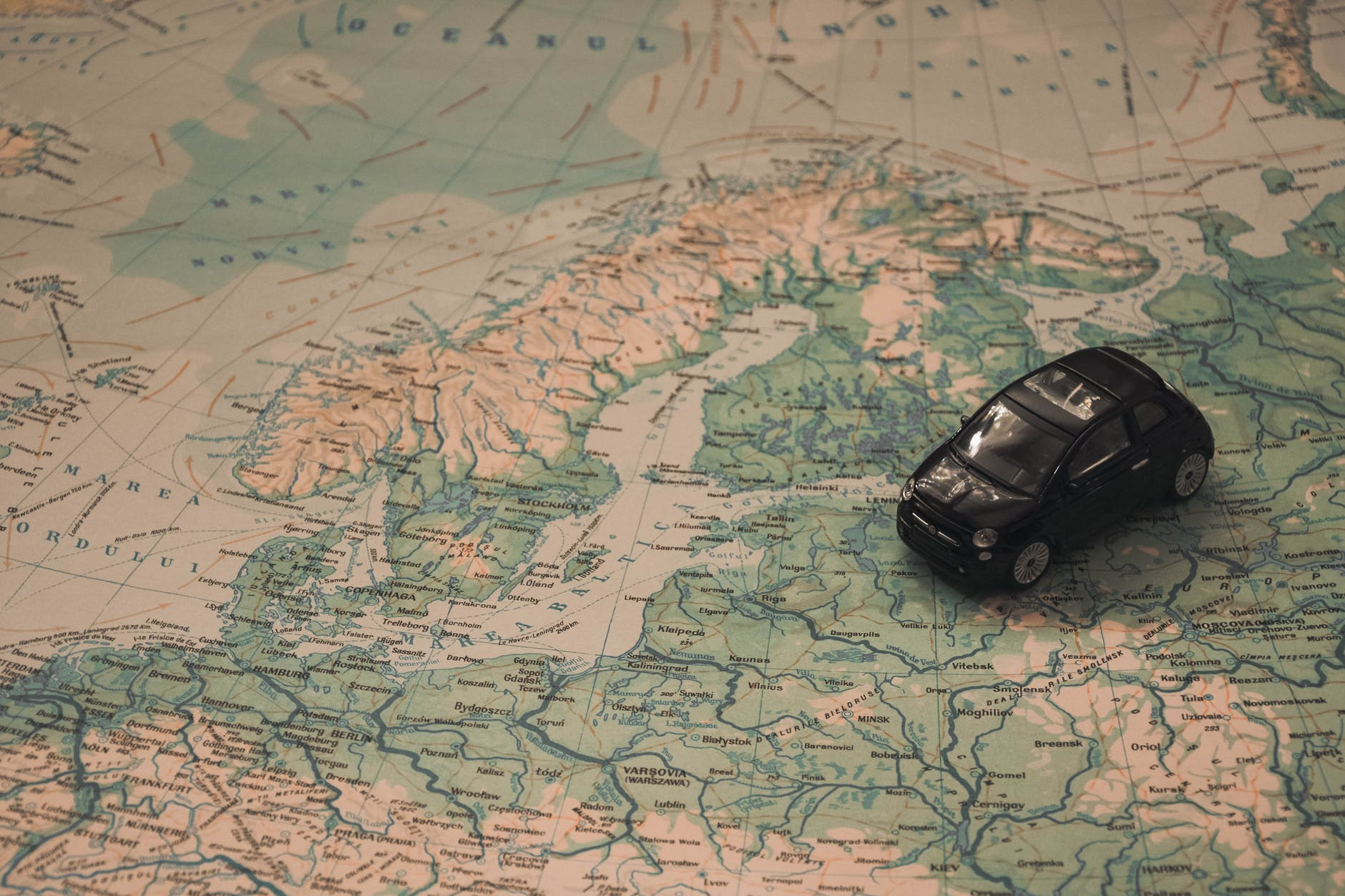 black toy car on world map paper