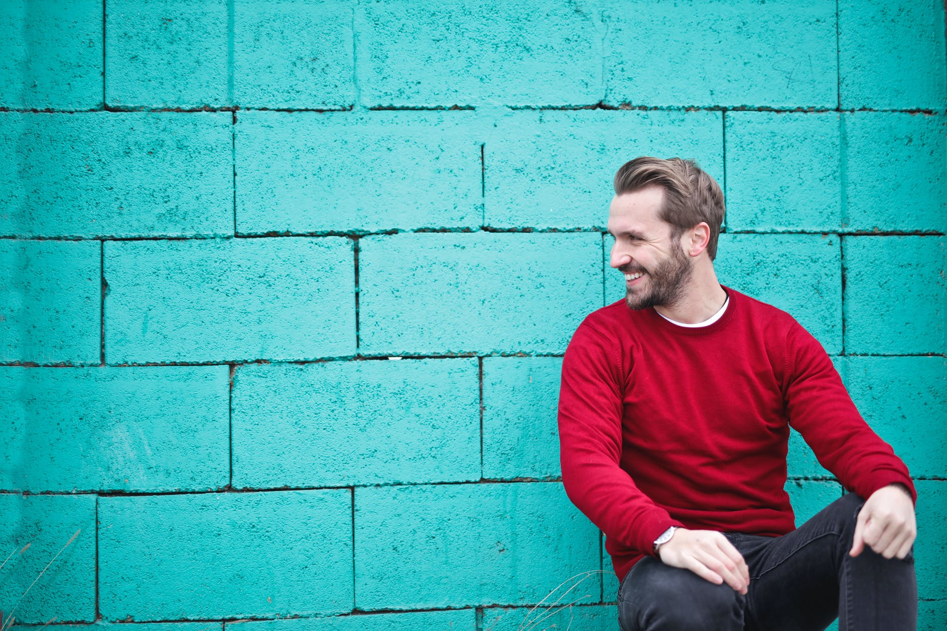 man wearing red sweatshirt and black pants leaning on the wall